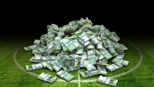 Geldbündel liegen auf einem Fußballplatz.