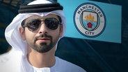Scheich Mansour bin Zayed Al Nahyan vor dem Logo von Manchester City (Montage) © picture alliance Foto: ZUMAPRESS.com