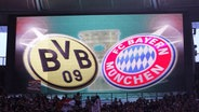Die Logos von Borussia Dortmund und Bayern München auf einer Anzeigetafel © imago/MIS